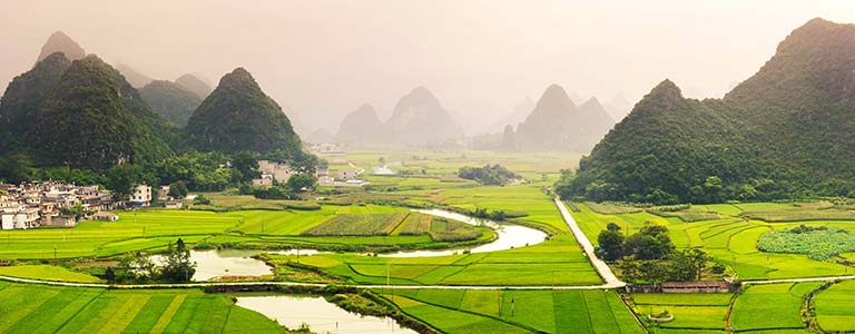 A Chinese village surrounded by green mountains and rice fields
