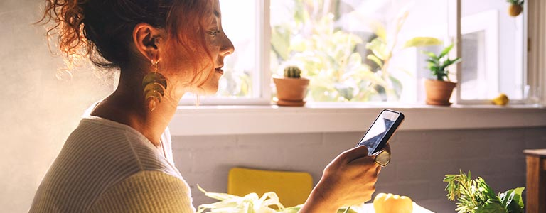 A woman browsing the Plant-Based Nutrition Certificate program on her phone.